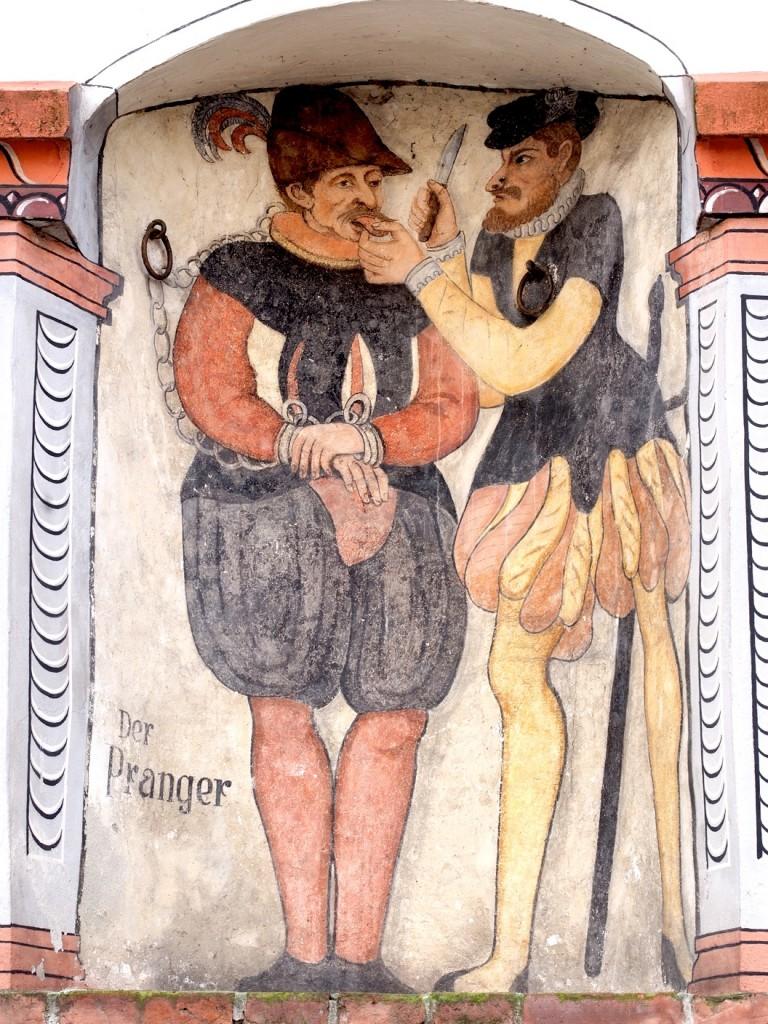 Die Abbildung eines Prangers in in Munderkingen an einer Fassade im Stadtkern.